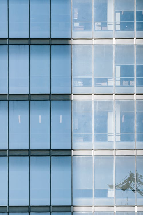 High multistory commerce building with reflecting glass windows covered with roller blinds from sunlight
