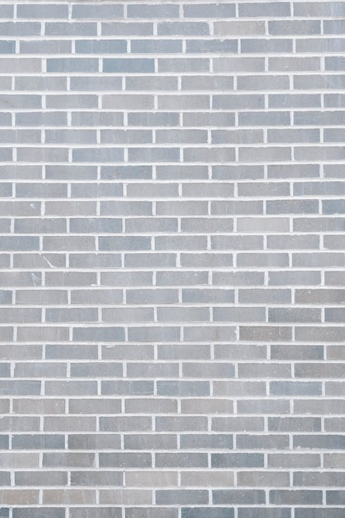 Full frame background of empty gray wall build with rows of brick blocks