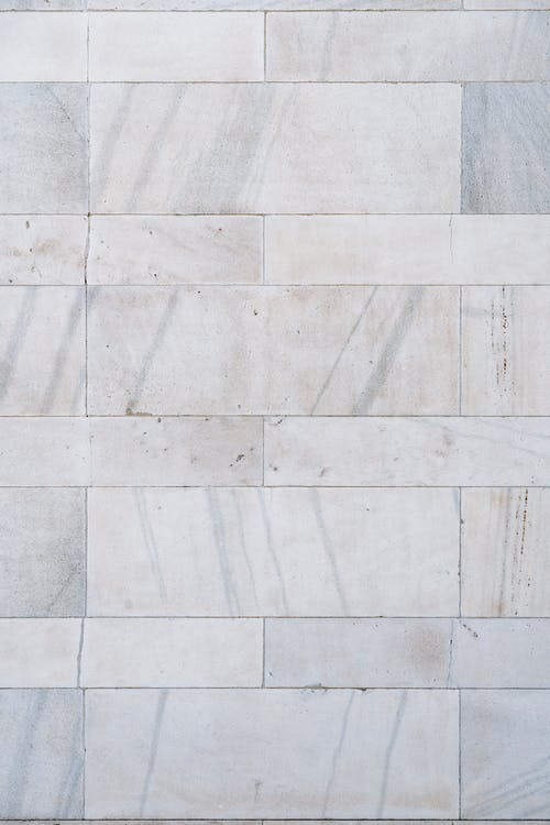 Full frame background of part of concrete wall with marble tiles with gray mottlings