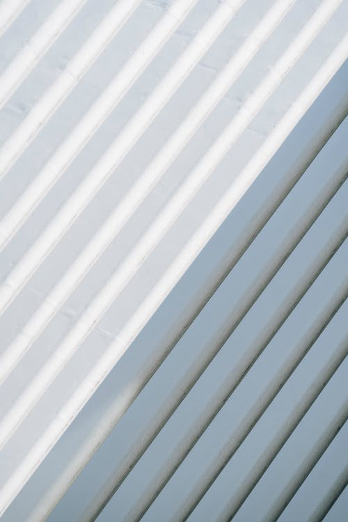 White wall with straight parallel metal parts with shadow from sunlight on concrete wall