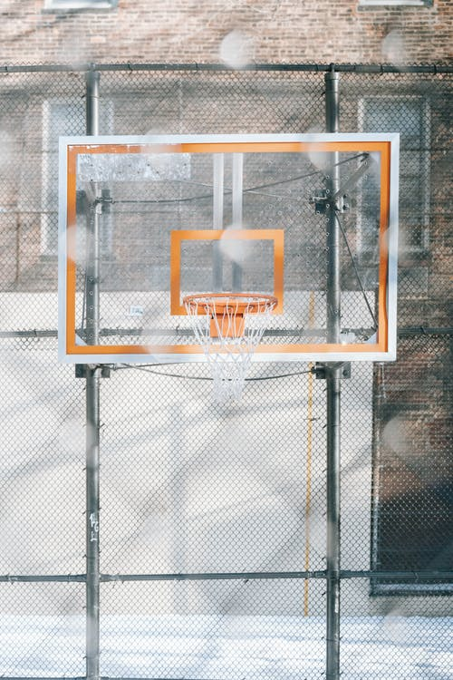 Basketball hoop hanging on backboard on sports ground