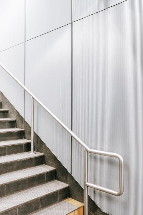 Staircase with metal railing and white wall