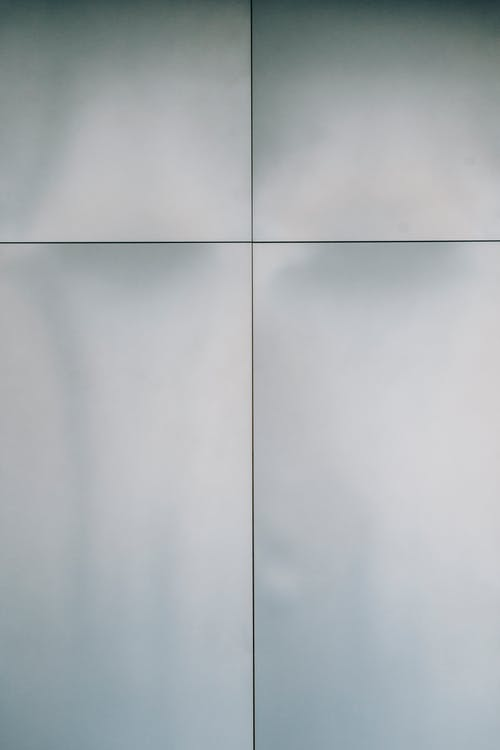 Full frame background of white textured wall with simple finishing panels and lines of modern residential building located on street