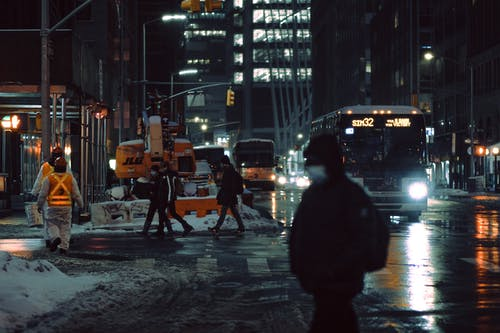 People in medical masks strolling on crosswalk near roadway with glowing buses on dark street during winter evening in city