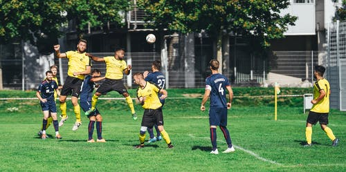 Young sportsmen playing football on outdoor field