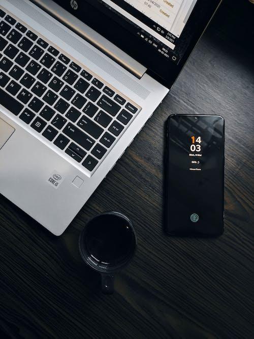 Black Iphone 5 Beside Macbook Pro