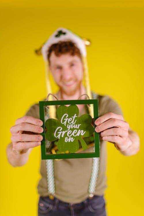 A Man Holding A Framed Clover Leaf