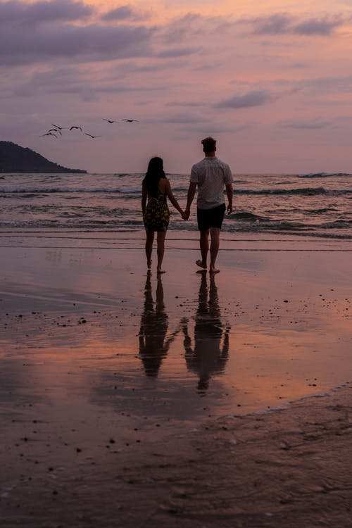 Back view full body of anonymous couple holding hands while standing on sandy coast near sea and admiring seascape under cloudy sky in evening