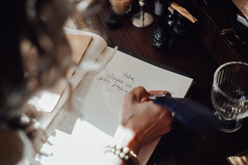 Crop author writing novel in copybook with feather at table