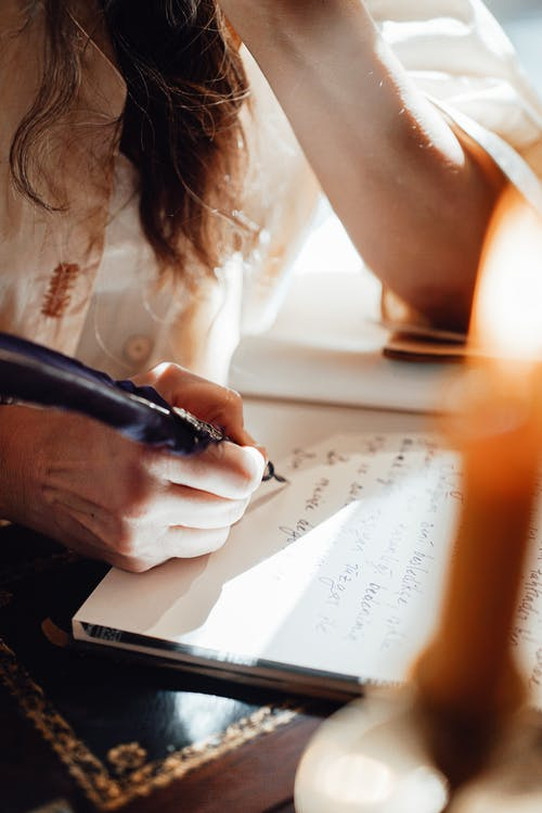 Faceless author writing novel in notepad with feather in sunbeam