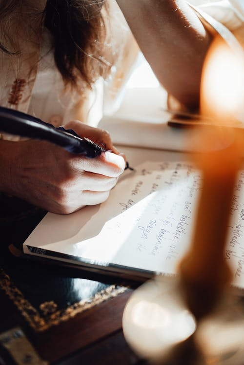 Crop unrecognizable female writer with feather taking notes in notepad at table on sunny day