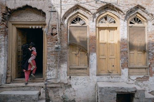 Woman in Black Dress Standing in Front of Brown Wooden Door