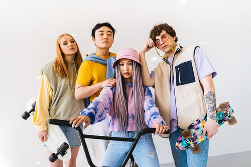 Group of People Wearing Casual Clothes With Their Skateboards and a Bicycle