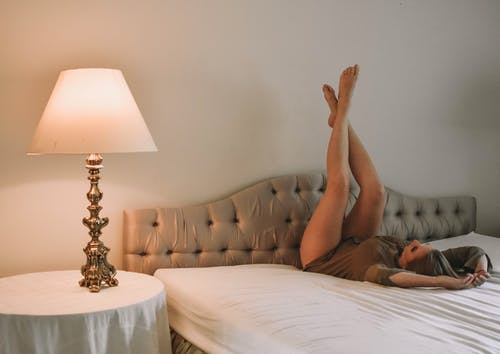 Seductive woman with raised legs lying on bed