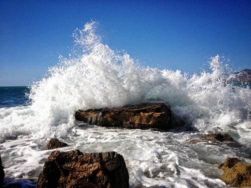 Rocky Seashore With Ocean Wave Under Blue Sky