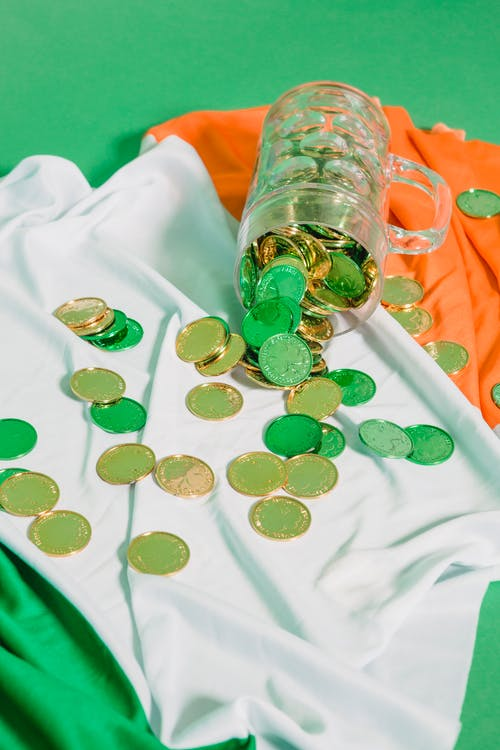 Glass with coins on Irish flag