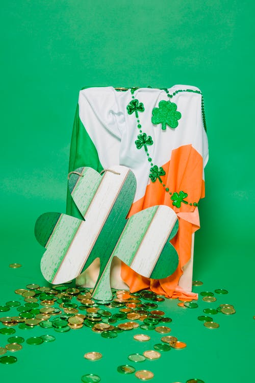 Composition of heap of gold coins placed near flag of Ireland with mirror in form of clover leaf on green background