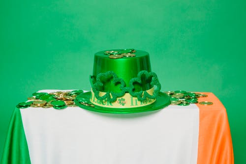 Green hat and coins on table with Irish flag