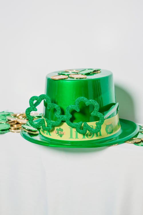 Shiny green hat with decorations and clover placed near heap of colorful coins on white background