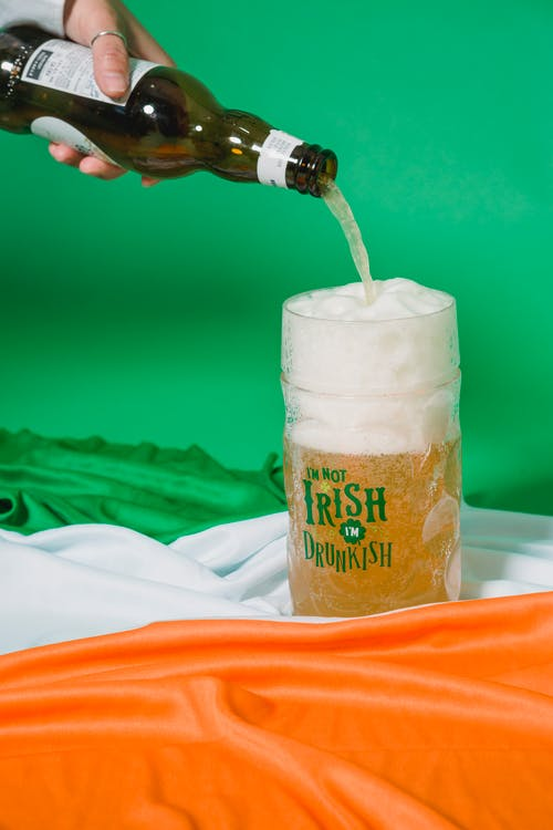 Crop anonymous person with ring pouring beer with froth from bottle into glass mug placed on Irish flag on green background