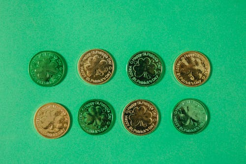 Top view of gold coins with clover pattern arranged in rows on light green surface