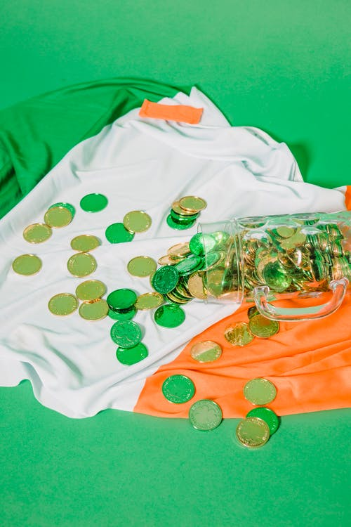 From above composition of glass jar with gold coins spread out on flag of Ireland on green background