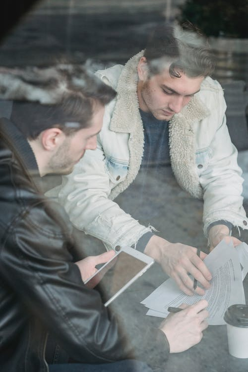 Through glass high angle of concentrated young men in casual clothes sitting at table and checking papers while working with tablet