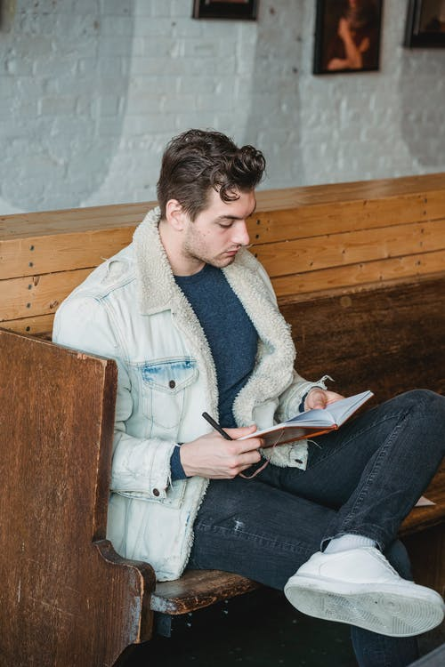 Serious man reading notes in notebook