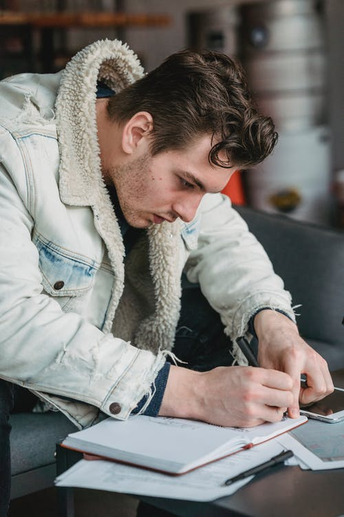 Focused male worker writing notes in notepad while sitting on sofa at table with tablet