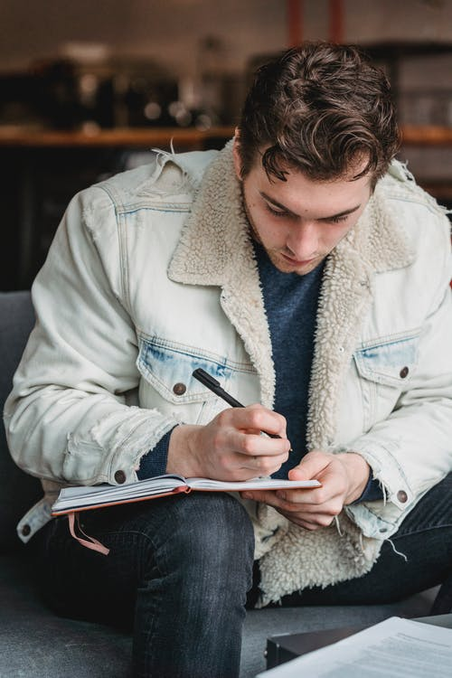 Stylish male in white warm denim jacket taking notes in planner sitting in cafe on blurred background
