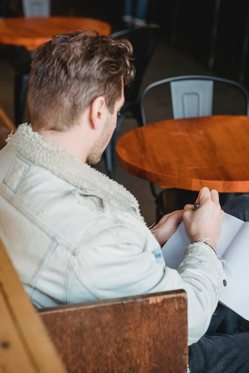 Crop anonymous male taking notes of new project in planner near round shaped timber table in cafe