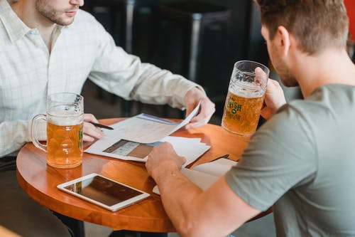 Crop unrecognizable men working with important papers at table with tablet with black screen and drinking beer