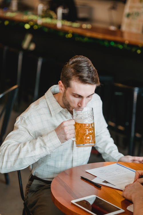 Pensive businessman drinking beer at table with papers near partner