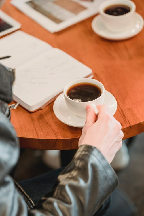 Man at table with cups of coffee and planner