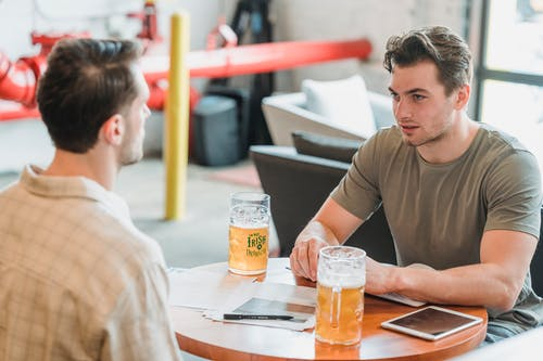 Young colleagues talking at table with documents having beer