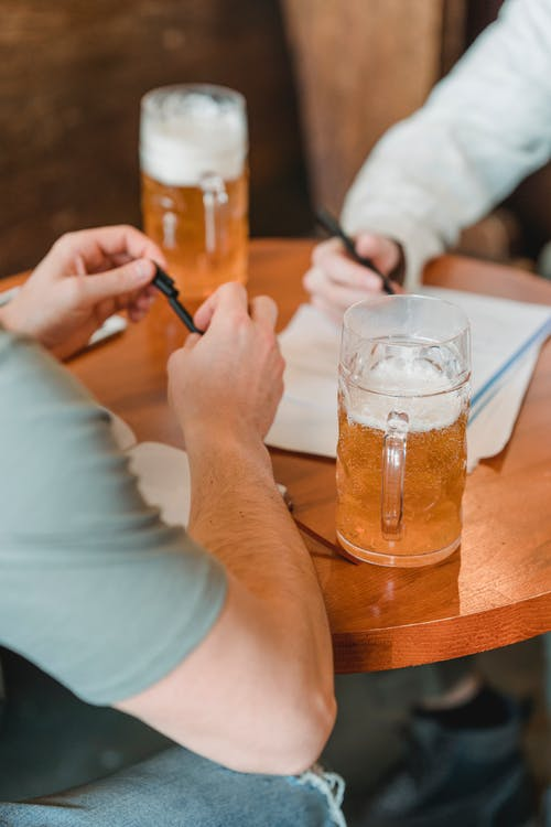 Crop unrecognizable men with pens and important papers at table on blurred background in pub