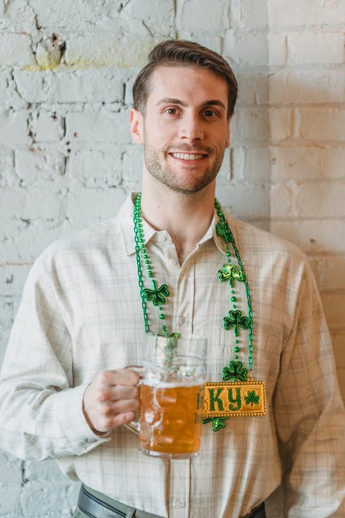 Positive bearded male in causal shirt and St Patricks day decorations smiling and looking at camera
