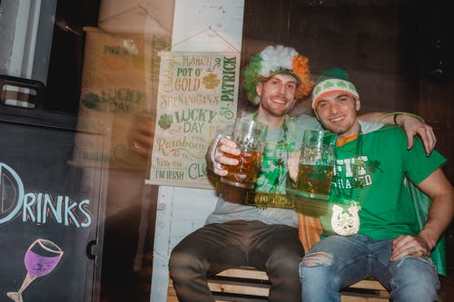 Through glass wall view of cheerful best male friends with beer embracing while looking at camera during Feast of Saint Patrick in pub