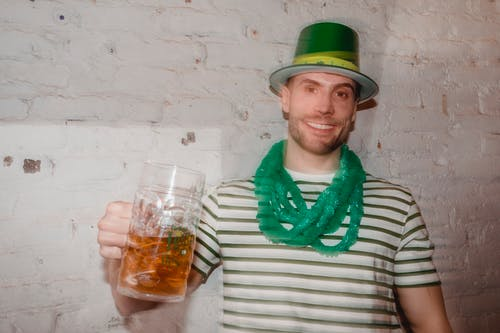 Through glass wall view of smiling male in shamrock hat looking at camera with jar of beer during Feast of Saint Patrick