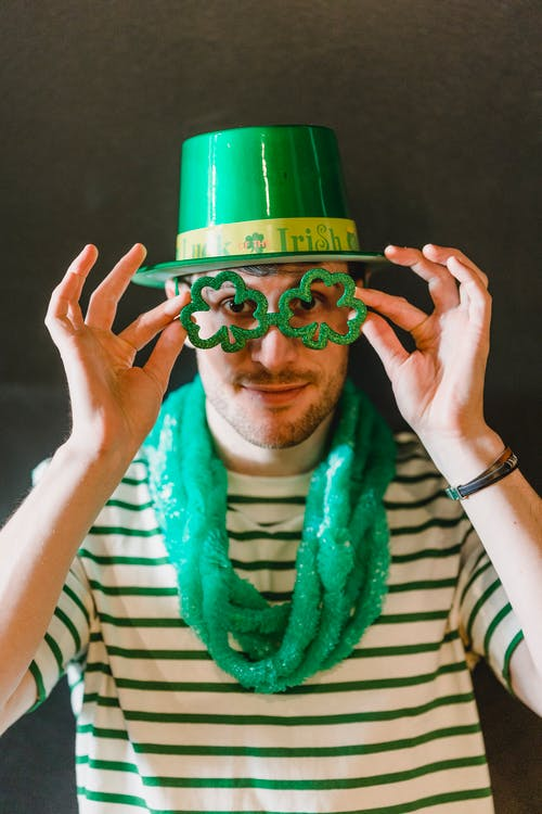 Male in shamrock hat with decorative eyeglasses looking at camera during Feast of Saint Patrick on gray background