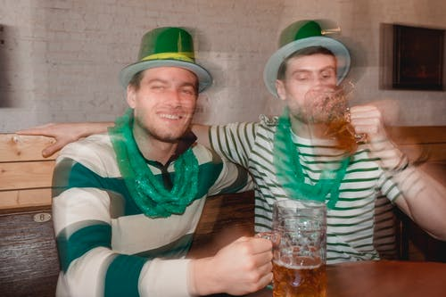 Through glass wall view of smiling man against partner enjoying beer from jar mugs at table during Feast of Saint Patrick in bar