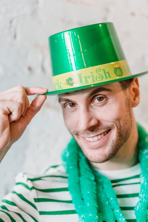 Sincere male in green hat looking at camera while celebrating Saint Patricks Day on blurred background