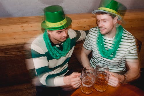 Drunk friends with beer celebrating St Patricks Day in pub