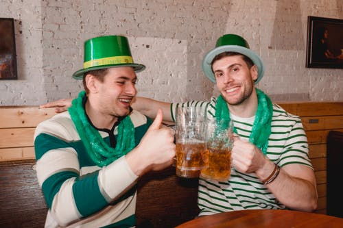 Happy friends clinking mugs of beer on Saint Patricks Day