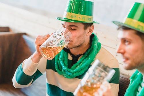 Crop best male friends in shamrock hats enjoying beer on bench on St Patricks Day