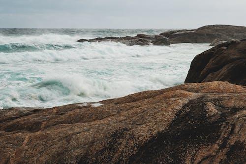 Foamy waves of stormy sea splashing near rocky formations