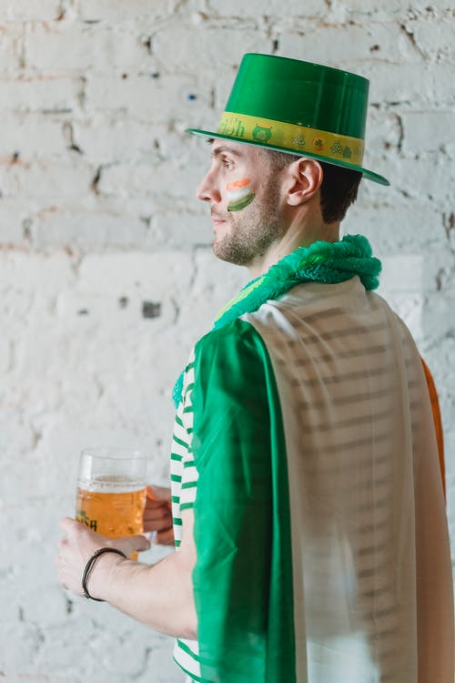 Back view of contemplative male in shamrock hat with jar of beer looking away against brick wall during Feast of Saint Patrick