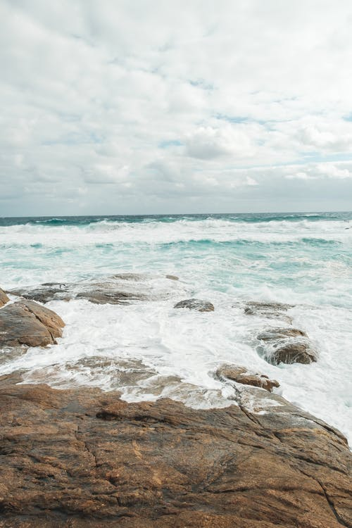 Picturesque view of azure foamy sea waves washing rocky stony coast under cloudy sky