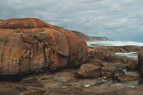 Rough rocky seashore with massive stones near stormy azure sea waving under gloomy cloudy sky