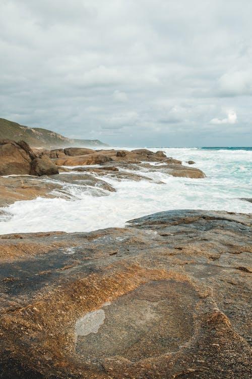 Foamy sea waves crashing on rocky seacoast